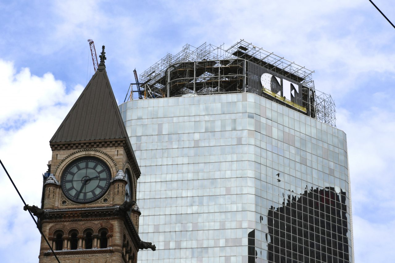 Workers install the Cadillac Fairview logo atop the Toronto CF headquarters