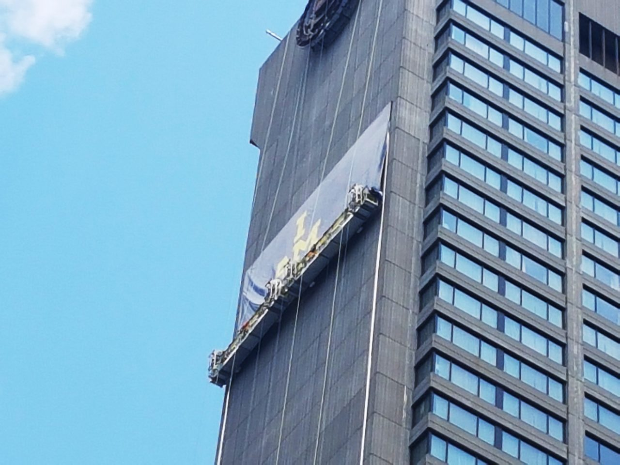 Workers on swing stages install the 22 storey Invictus Games print banner