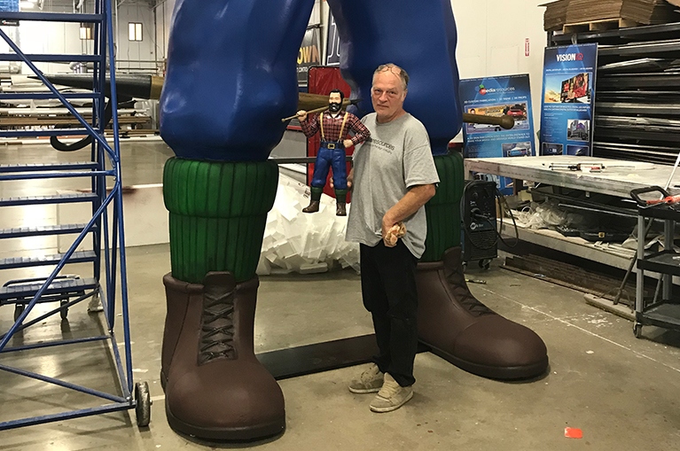 Our in-house sculptor holding a prototype standing next to full size