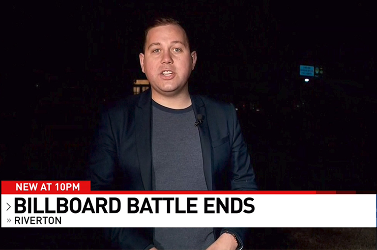 "News anchor stands in front of a dim billboard with the headline ""Billboard Battle Ends"""