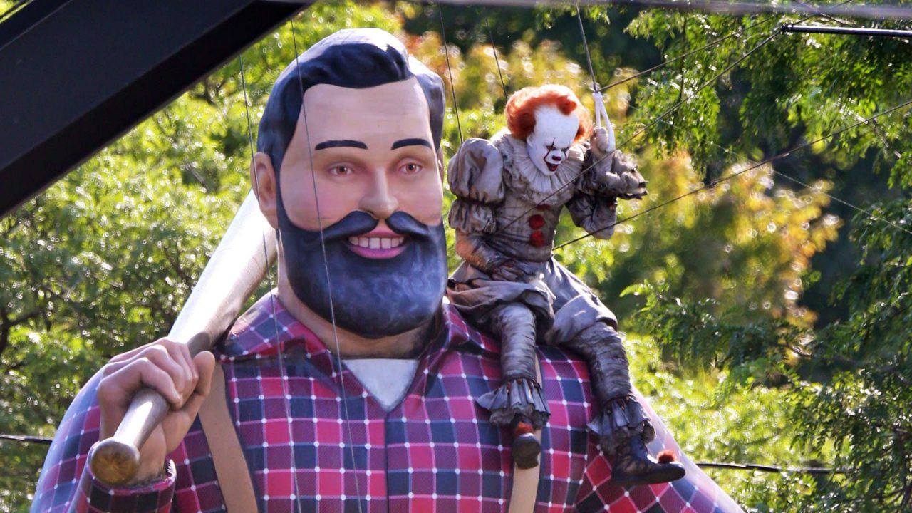 """Bill Skarsgard dressed as Pennywise the Clown atop 3D printed Paul Bunyan statue while filming """"IT: Chapter 2"""" in Toronto, ON"""