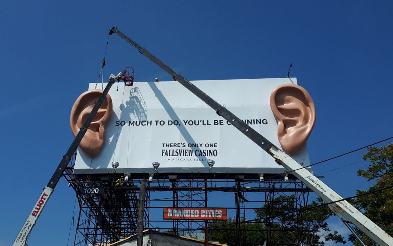 """Installation of 3D ears billboard extension for Fallsview Casino campaign """"grinning from ear to ear"""""""