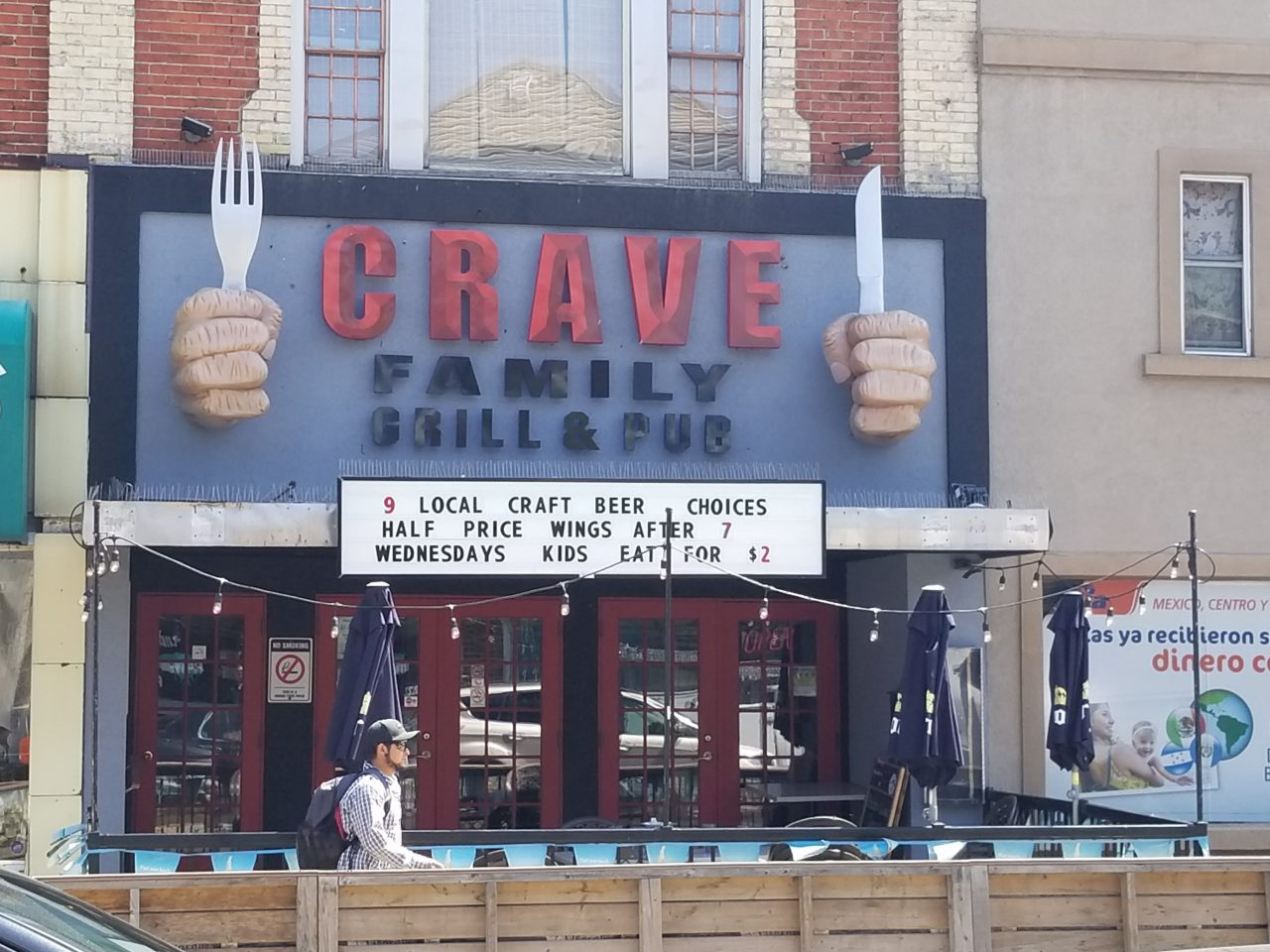 3D Hands and utensils storefront for Crave Family Grill & Pub