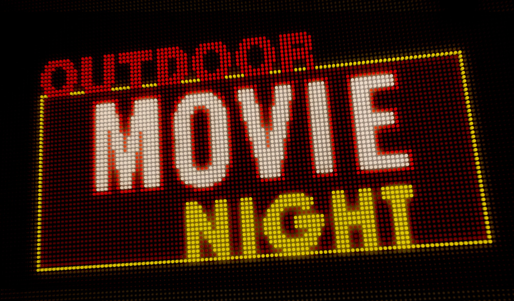 Outdoor Movie Night Retro Intro Illuminated Letters on Big Neon Display With Large Pixels.