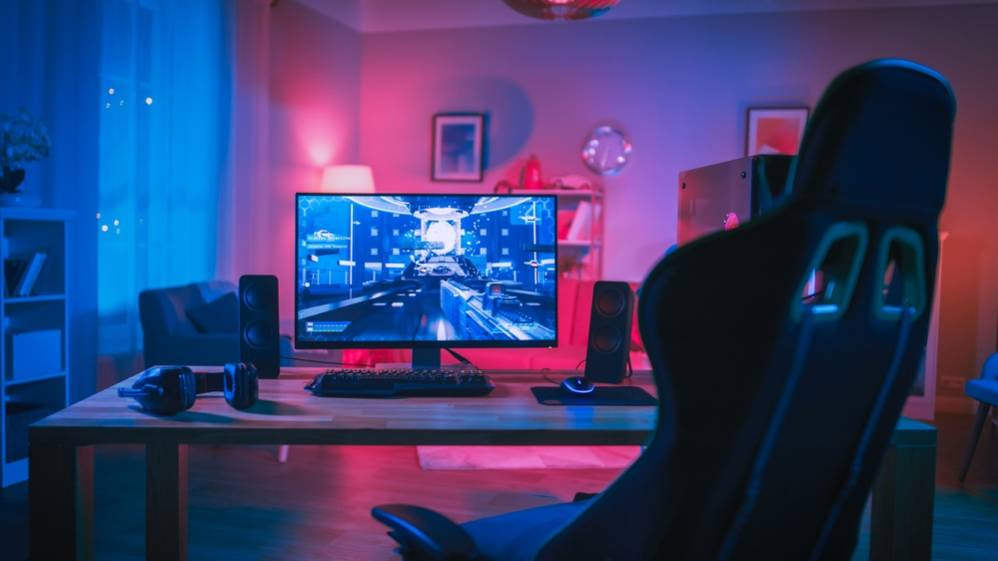 Monitor Stands on the Table at Home. Cozy Room With Modern Design Is Lit With Pink Neon Light.