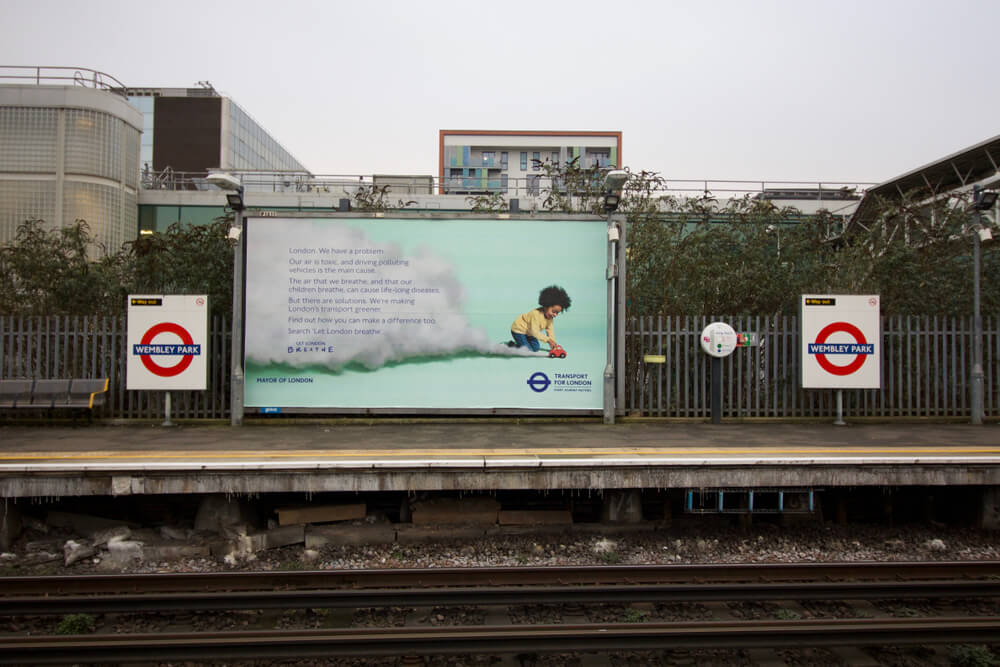 Advertising Hoarding at Underground Station Regarding Air Pollution and Toxic Air in London With Platform and Rails in the Foreground