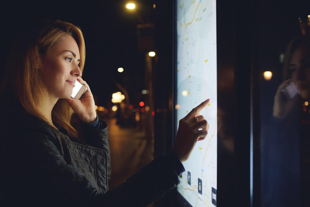 Pretty Woman Tourist Talking on Mobile Phone While Looks at Map of the City on Electronic Bulletin Board